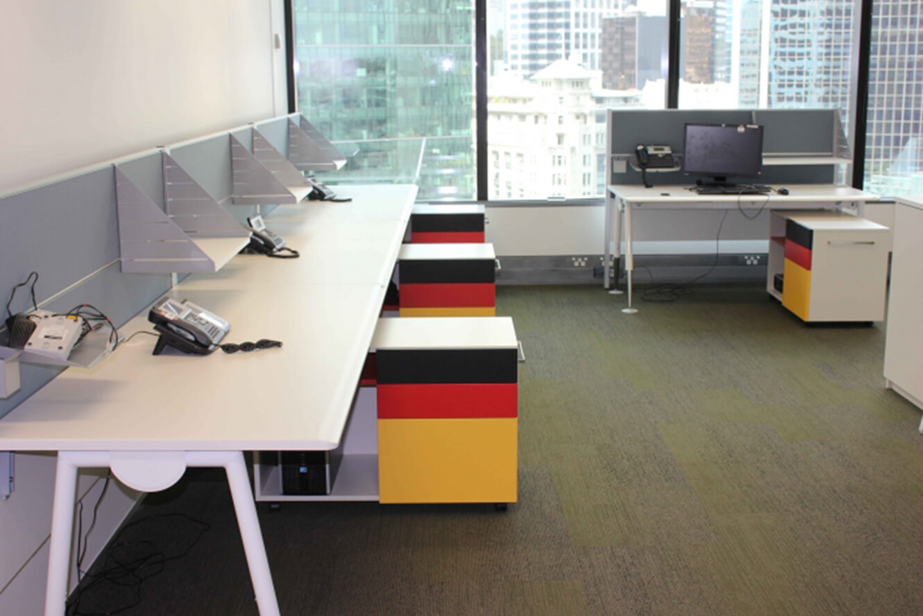 white desks with coloured mobile cadies. Black, red and yellow