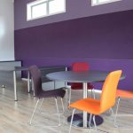 meeting table with orange and purple chairs. workstation in back ground