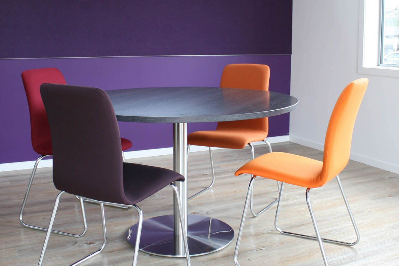 meeting table with orange and purple chairs
